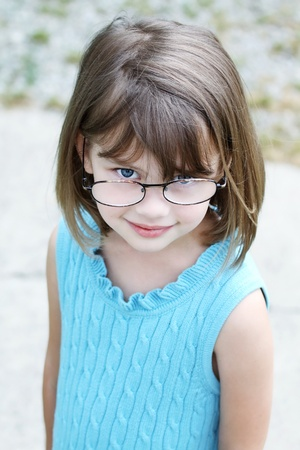 Little girl outdoors wearing glasses and looking up into the camera.