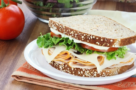 Smoked chicken sandwich with lettuce, tomato and swiss cheese and whole grain bread.  photo