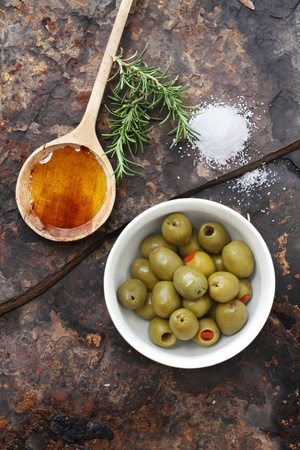 Spanish olives with olive oil, rosemary, sea salt and olive on a rustic slate background.