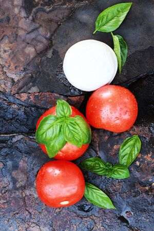 Ingredients for Caprese Salad. Mozzarella cheese, fresh basil, and tomatoes on a rustic slate background.  photo