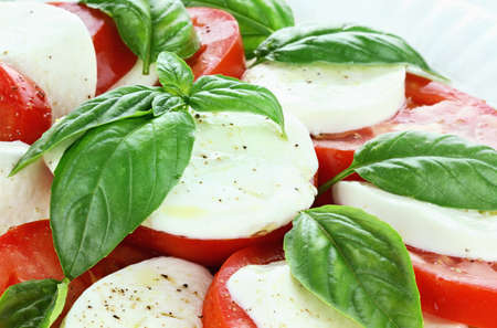 Caprese Salad prepared with mozzarella cheese, fresh organic basil, and tomatoes and then seasoned with olive oil, salt and cracked pepper.  photo