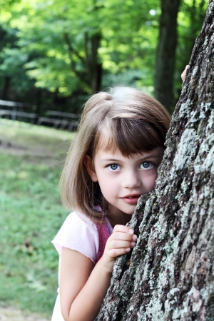 Little girl leaning against a large oak tree and looking at the viewer. Stock Photo