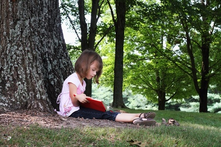 five year: Little girl sits outdoors under a large oak tree and reads a book.