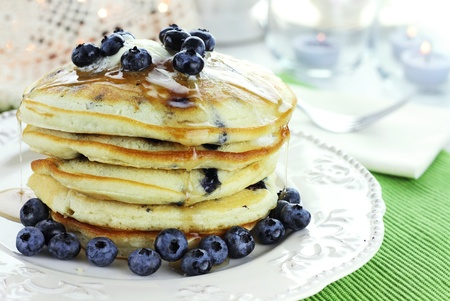 Stack of fresh pancakes dripping with butter and maple syrup. Garnished with fresh blueberries.