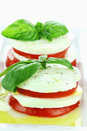 Delicious Caprese Salad made with mozzarella cheese, fresh basil, and tomatoes. photo