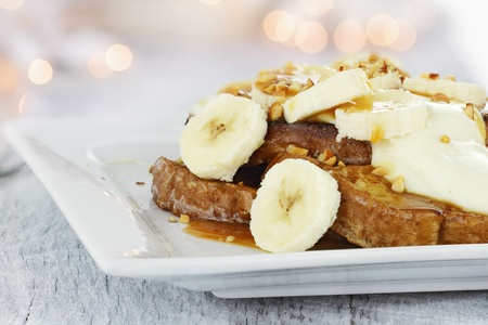 banana bread: French toast topped with sliced bananas, nuts, cream cheese sauce and caramel syrup. Extreme shallow depth of field with selective focus.