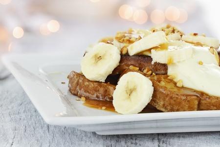 cuisine fran�aise: Toasts fran�ais garni de tranches de banane, de noix, sauce au fromage � la cr�me et le sirop de caramel. Extreme profondeur de champ avec un accent s�lectif.