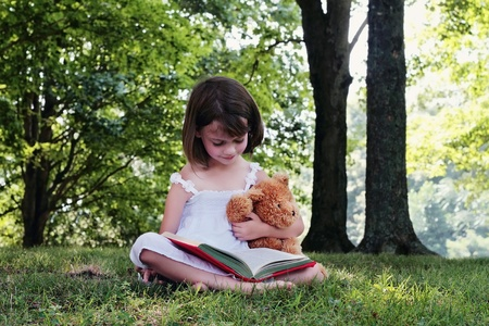 Girl reading outdoors to her little teddy bear.