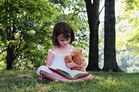 bambini che leggono: Ragazza di lettura all'aperto per il suo piccolo orsacchiotto.