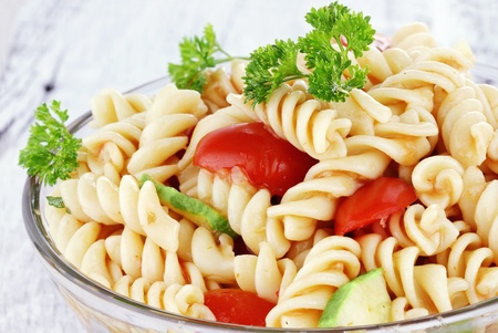 pasta salad: Pasta salad with dressing, fresh tomatoes, cucumbers and parsley. Shallow depth of field.
