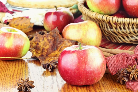 'cinnamon bark': Red apple with anise stars and cinnamon bark. Basket of apples and fresh apple pie in the background. Extreme shallow depth of field with focus on the foreground.