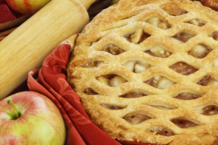 Delicious fresh baked apple pie with rolling pin and ingredients. Perfect for the holidays. photo