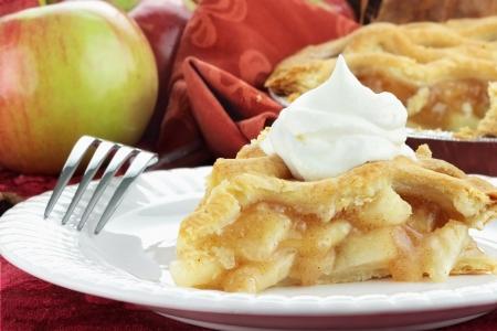 ホイップ クリームとおいしいの新鮮な焼きリンゴのパイのスライス。極端な浅い被写し界深度のパイのスライスの選択的な焦点と。