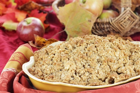 Freshly baked apple crisp with fresh apples and autumn leaves in the background. Shallow depth of field with selective focus on the foreground. photo