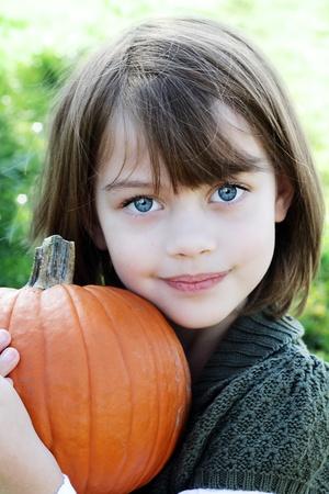 Little girl holding a pumpkin close to herself.