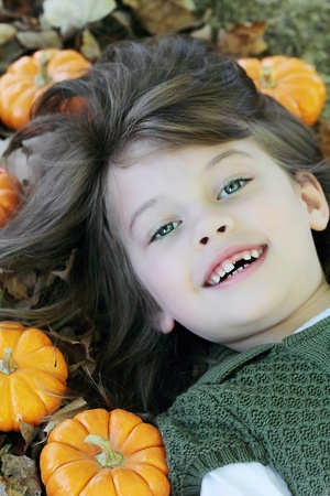 Child lying in autumn leaves and pumpkins. photo