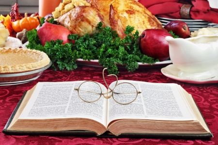 christmas dish: Open Bible with glasses lying on a holiday dinner table with prepared turkey and fixings in background.