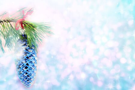 Christmas tree branch holding a pine cone ornament against a beautiful blue background with copyspace.   photo