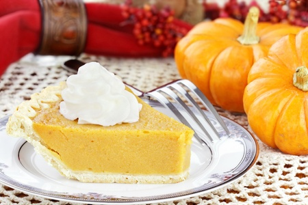 A slice of sweet potato or pumpkin pie with whipped cream. Selective focus on pie.     photo