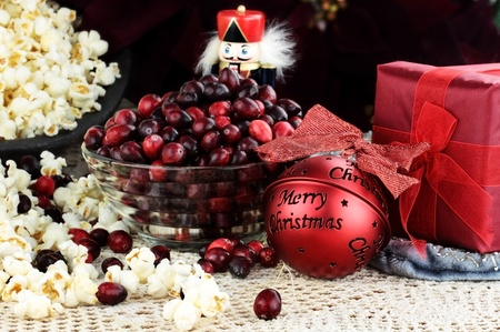 String of popcorn and cranberries with bowl of cranberries, popcorn, gift and ornaments in background. Shallow depth of field.   photo