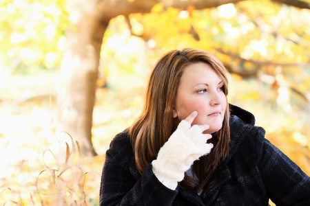 Beautiful young thoughtful woman sitting outdoors on a gorgeous autumn day. photo