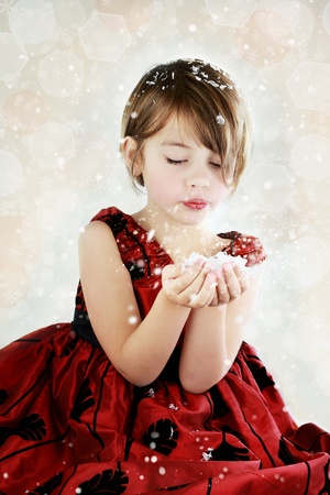 Little girl dressed up for the holidays blows snow from her hands.