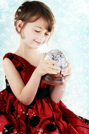 Happy little girl holding a snow globe. photo