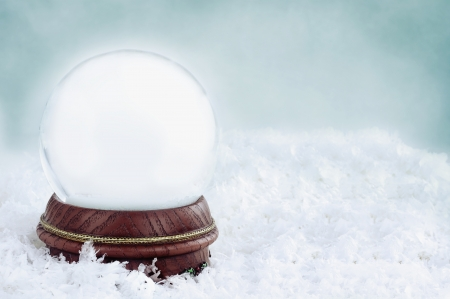 Blank snow globe with with copy space available against a blue background. photo