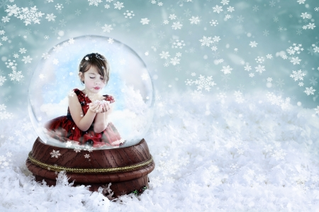 Little girl inside a snow globe blowing snow out of her hands. Copy space available. photo