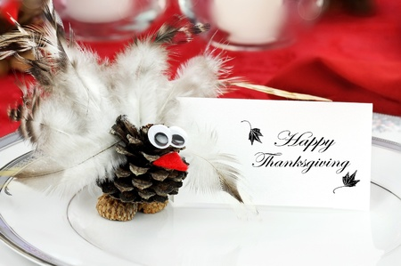 Cute little turkey sits by a place card  on a holiday table for Thanksgiving Day. photo