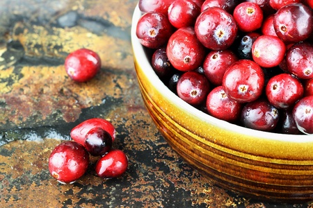 Freshly washed whole cranberries against a rustic background with selective focus.