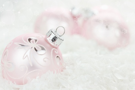 Pink Christmas baubles lying in the snow. Shallow depth of field. photo