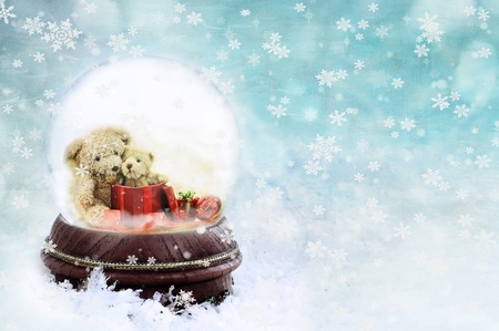 Two adorable little teddies inside of a snow globe against a blue background. photo