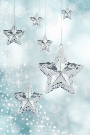 Hanging silver Christmas star ornaments against a festive blue background.