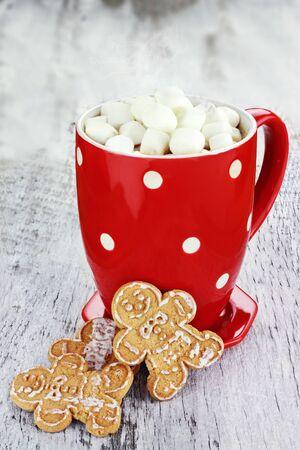 chocolate caliente: Taza de chocolate caliente con malvaviscos y galletas sobre un fondo rústico. Foto de archivo