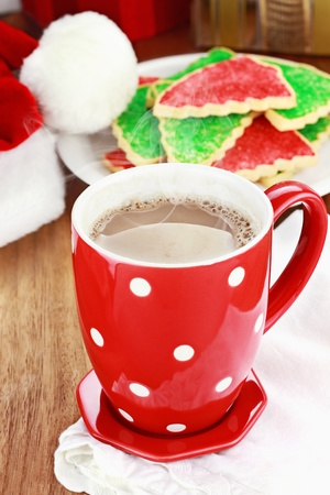 Cup of hot cocoa with Christmas cookies and Santas hat in the background. Shallow depth of field.