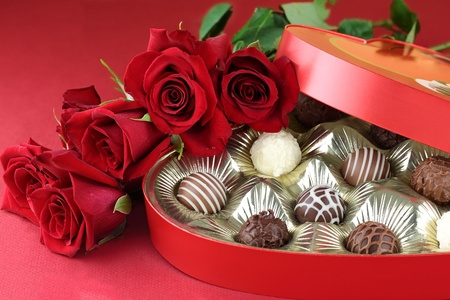 box of chocolates: Heart shaped box filled with a variety of candies and long stem roses against a red background. Selective focus on candy.