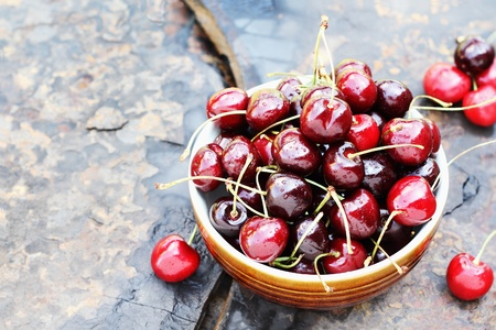 Bowl of black cherries with stems over a rustic background with available copy space.