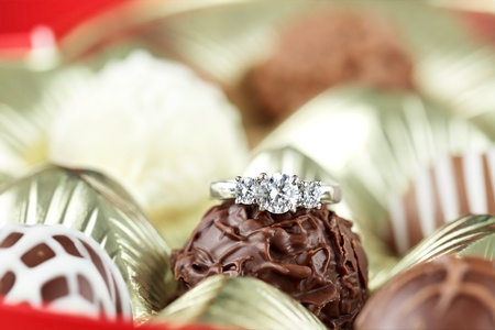 proposal of marriage: Diamond engagement inside of a box of chocolate truffles. Extreme shallow depth of field with selective focus on diamond ring.