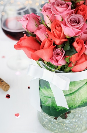 red rose bokeh: Bouquet of roses against a romantic table setting. Selective focus on roses blossoms with blur on lower portion of image. Stock Photo