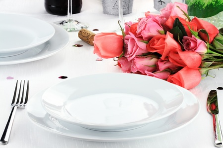Romantic table setting for two with a bouquet of roses.