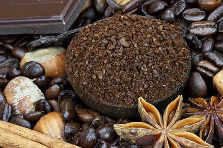 'cinnamon bark': Background of gourmet coffee ingredients: coffee beans, ground coffee, hazelnuts, vanilla and cinnamon bark. Stock Photo
