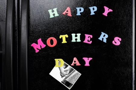 fridge: Refrigerator magnets with the message of Happy Mothers Day and a photo of a father and child holding hands. Stock Photo