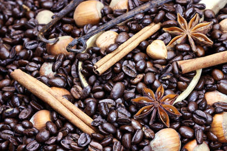 Background of gourmet coffee ingredients: coffee beans, ground coffee, hazelnuts, vanilla and cinnamon bark in a wooden spoon.