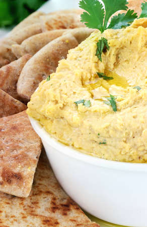 Bowl of hummus topped with pure olive oil and cilantro and served with wedges of pita bread for a healthy snack. photo