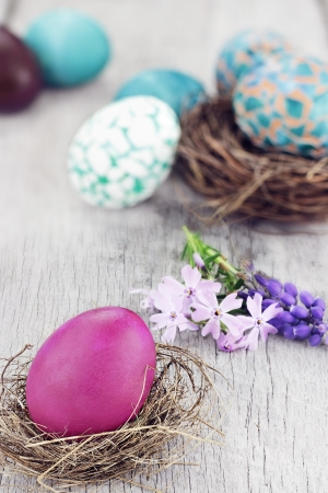 Beautiful Easter egg in a small nest with spring flowers and more eggs in background. Selective focus on egg in foreground. photo