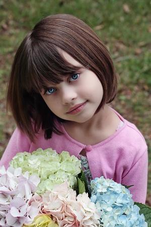 Mooi meisje meteen bosje pastelkleurige hortensia's voor haar moeder op Moederdag.