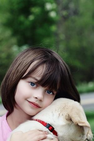 pet photography: Little girl holding her puppy, an English Cream Labrador Golden retriever mix.