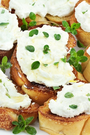 Bruschetta with ricotta cheese, lemon zest and thyme, drizzled with golden honey. Selective focus on center Bruschetta and some blur on lower portion of image.