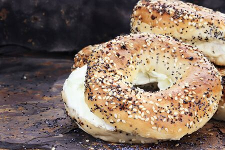 Stack of bagels and cream cheese against a rustic slate background.  Stock Photo